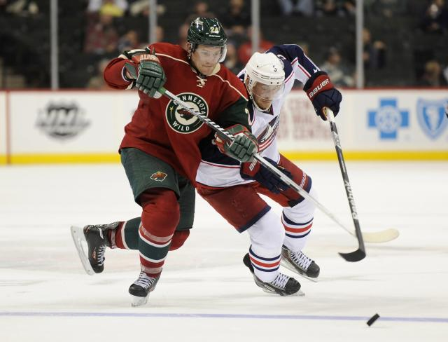 ST PAUL, MN - SEPTEMBER 17: Matt Cooke #24 of the Minnesota Wild and Jack Skille #5 of the Columbus Blue Jackets go after the puck during the third period of the preseason game on September 17, 2013 at Xcel Energy Center in St Paul, Minnesota. The Blue Jackets defeated the Wild 3-1. (Photo by Hannah Foslien/Getty Images)