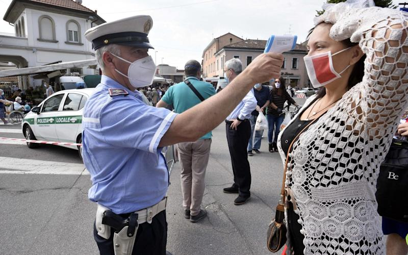 A police officer checks the body temperature of a woman at a market in Treviglio, near Bergamo, northern Italy - Shutterstock