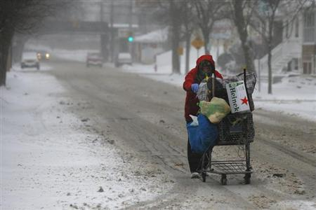 A man pushes a cart up the road while scavenging for bottles and cans during a winter nor'easter snowstorm in Lynn
