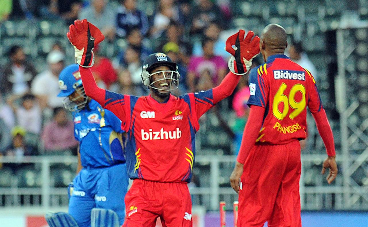 Highveld Lions wicket keeper Thami Tsolekile congratulates bowler Aaron Phangiso for the wicket of Mumbai Indians batsman Sachin Tendulkar   during Group B  Match of The Champions League T20 (CLT20)  at Wanderers Stadium in Johannesburg on October 14, 2012. AFP PHOTO / ALEXANDER JOE