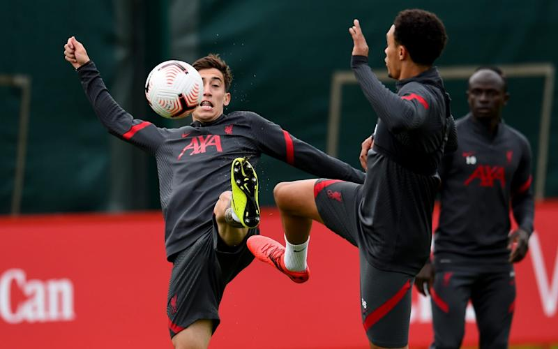 Kostas Tsimikas and Trent Alexander-Arnold battle for the ball in training  - GETTY IMAGES