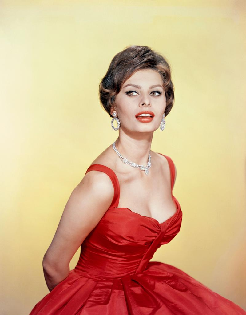 Posing for a photo in a red dress,circa 1955.