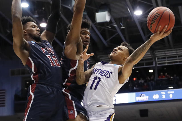 Prairie View A&M's Dennis Jones (11) shoots against Fairleigh Dickinson's Mike Holloway Jr., center, and Kaleb Bishop (12) during the second half of a First Four game of the NCAA college basketball tournament, Tuesday, March 19, 2019, in Dayton, Ohio. (AP Photo/John Minchillo)