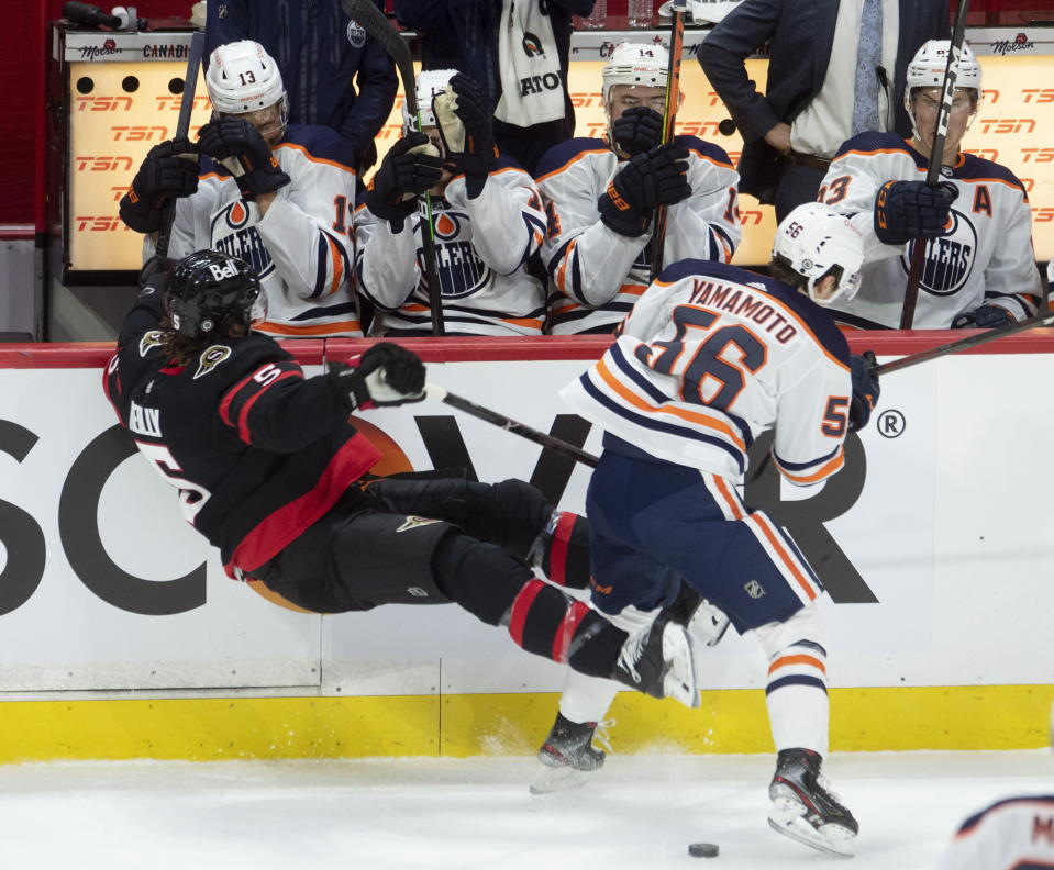 Players on the bench cover up as Edmonton Oilers right wing Kailer Yamamoto sends Ottawa Senators defenseman Mike Reilly into the boards during the first period of an NHL hockey game Wednesday, April 7, 2021, in Ottawa, Ontario. (Adrian Wyld/The Canadian Press via AP)
