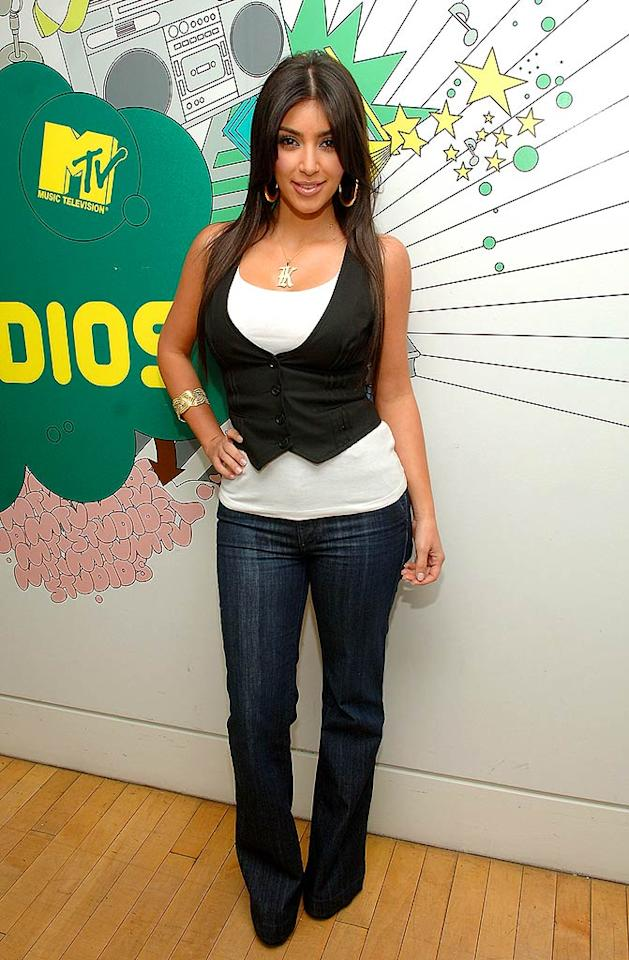 """Reality vixen Kim Kardashian strikes her trademark pose on MTV's """"TRL"""": lips parsed, chest out, hand on hip. Jamie McCarthy/<a href=""""http://www.wireimage.com"""" target=""""new"""">WireImage.com</a> - March 10, 2008"""