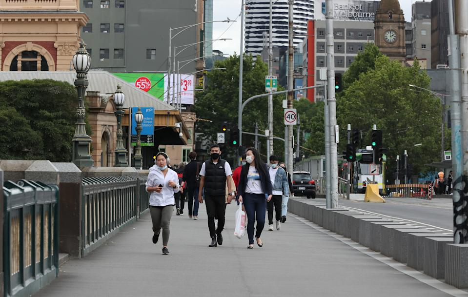 MELBOURNE, AUSTRALIA - NOVEMBER 06: A general view of pedestrians crossing the bridge with the CBD in the background on November 06, 2020 in Melbourne, Australia. Lockdown restrictions in Melbourne were lifted on 28 October, with people now able to leave their homes for any reason. Cafes, restaurants, pubs and bars can reopen subject to patron limits while beauty services, tattoo parlours and any other service where you can wear a mask will be able to resume. Up to 10 people from any number of households will be able to gather outdoors, however, Victorians are still required to wear a face mask in public.  (Photo by Asanka Ratnayake/Getty Images)