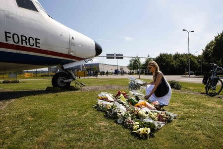 A local woman lays a bouquet of flower on the grass in front of a Dutch airplane during a national day of mourning for the victims killed in Malaysia Airlines Flight MH17 plane disaster last Thursday, in Eindhoven July 23, 2014. REUTERS/Mischa Rapmund