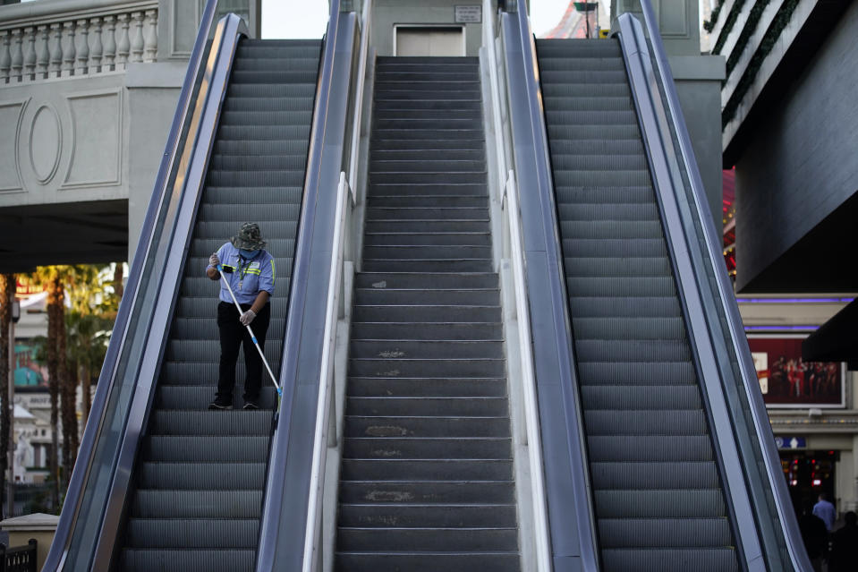 A worker cleans an escalator along the Las Vegas Strip, Thursday, Nov. 19, 2020, in Las Vegas. As the coronavirus surges to record levels in Nevada, the governor has implored residents to stay home. But Democrat Steve Sisolak has also encouraged out-of-state visitors, the lifeblood of Nevada's limping economy, to come to his state and spend money in Las Vegas. (AP Photo/John Locher)