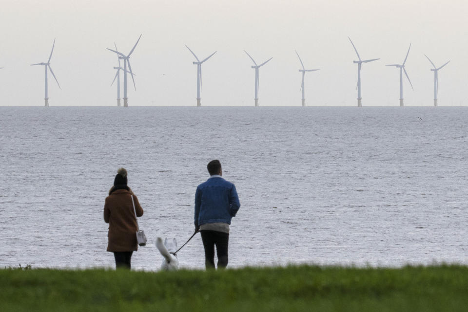 Some lenders are starting to offer green mortgages with incentives such as lower interest rates for less wasteful buildings. Above, a couple look out at wind turbines off the coast of Essex in Frinton-on-Sea, England. Photo: Dan Kitwood/Getty Images