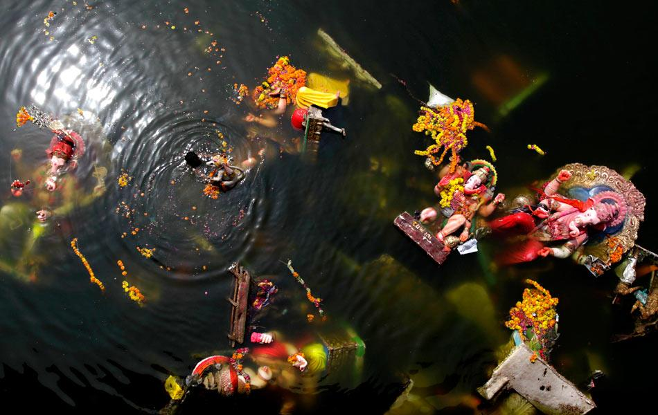 A man searches for reusable items amid immersed idols of the elephant-headed Hindu God Ganesh in the Sabarmati River. Action groups in Mumbai insist that there is a silver lining amid all of this: In 2009, 8,383 household idols were immersed in artificial ponds. In 2010, they maintain, the number grew to 13,866.