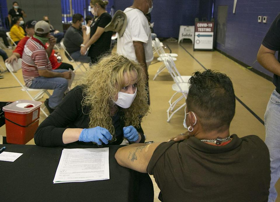 Arizona Department of Health Services Director Dr. Cara M. Christ talks to a person after giving them a COVID-19 vaccine at Grant Park Recreation Center in Phoenix.