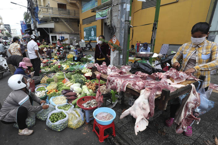 Local vendors sell pork meat and vegetables on a sidewalk as the main market remained closed during a lockdown, following a battling against a surge of COVID-19 cases, in downtown Phnom Penh, Cambodia, Wednesday, May 26, 2021. (AP Photo/Heng Sinith)