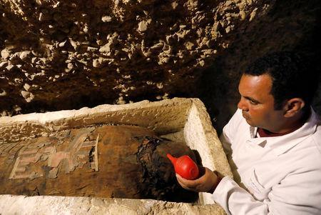 A Egyptian archaeologist is seen next to a coffin inside a tomb during the presentation of a new discovery at Tuna el-Gebel archaeological site in Minya Governorate, Egypt, February 2, 2019. REUTERS/Amr Abdallah Dalsh