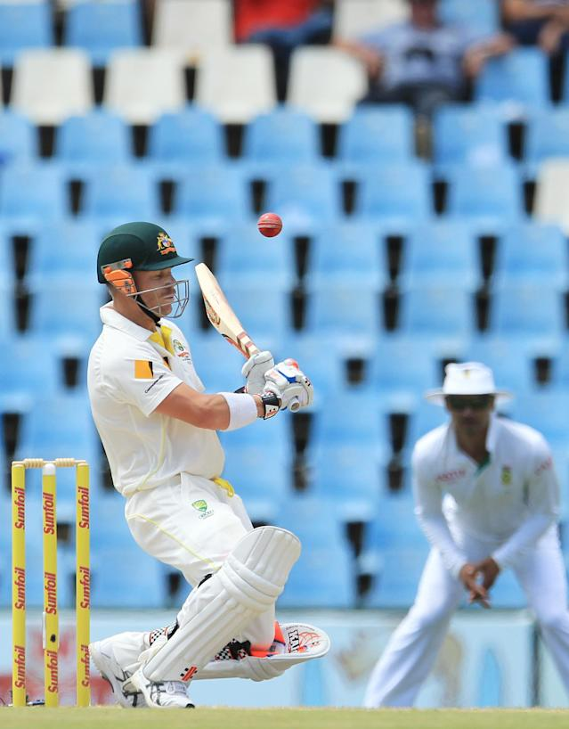 Australia's batsman David Warner, left, avoids a bouncer as South Africa's Alviro Petersen, right, watches on the third day of their their cricket test match at Centurion Park in Pretoria, South Africa, Friday, Feb. 14, 2014. (AP Photo/ Themba Hadebe)