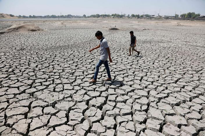 Indian boys on their way to play cricket walk through a dried patch of Chandola Lake in Ahmadabad, India, on May 14, 2016. In 2016, much of India suffered from a heat wave that lasted for weeks, along with a severe drought that has decimated crops, killed livestock and left at least 330 million Indians without enough water for their daily needs.