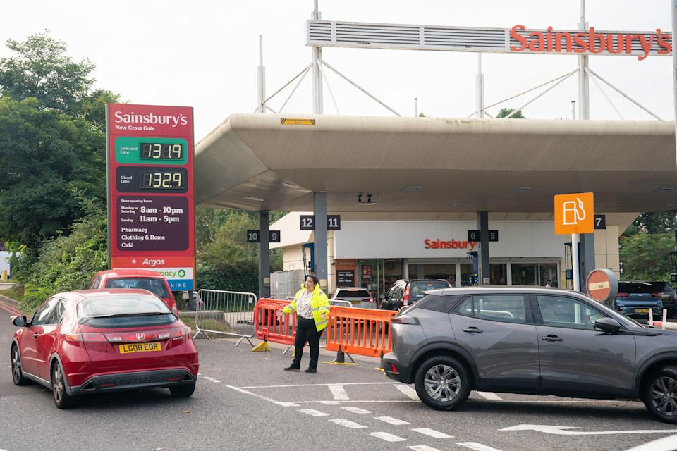 A member of staff directs motorists trying to queue for fuel at a Sainsbury's petrol station in south London (PA)