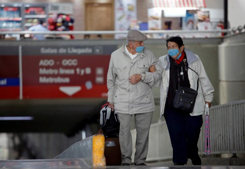 An elderly couple wearing protective masks arrives at the TAPO bus terminal in Mexico City