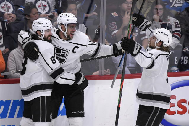 Los Angeles Kings' Anze Kopitar (11) celebrates his goal against the Winnipeg Jets with Drew Doughty (8) and Adrian Kempe (9) during the third period of an NHL hockey game Tuesday, Oct. 22, 2019, in Winnipeg, Manitoba. (Fred Greenslade/The Canadian Press via AP)