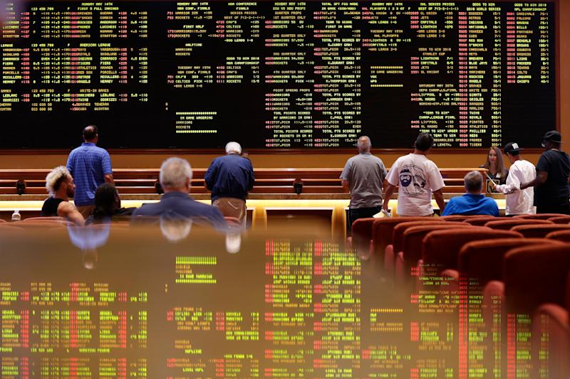 FILE - In this May 14, 2018 file photo, people make bets in the sports book at the South Point hotel and casino in Las Vegas. Las Vegas is not worried about the competition from casinos in other states that for the first time Sunday, Feb. 3, 2019, will also offer football fans a chance to bet on the Super Bowl. The weekend is worth hundreds of millions of dollars to the city, which draws tens of thousands of people for the big game's weekend. (AP Photo/John Locher, File)