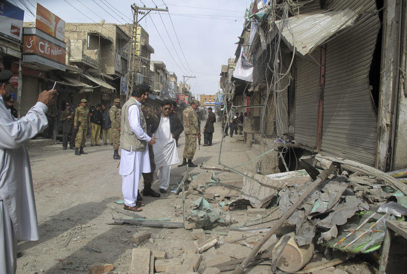 Pakistani security officials check the site of a bomb blast as the minority Muslim Shia sect observes the annual Ashoura holiday in Dera Ismail Khan, Pakistan, Sunday, Nov. 25, 2012. A bombing claimed by the Taliban killed several people at a Shiite religious procession in northwestern Pakistan on Sunday, police said. (AP Photo/Kashif Naveed)