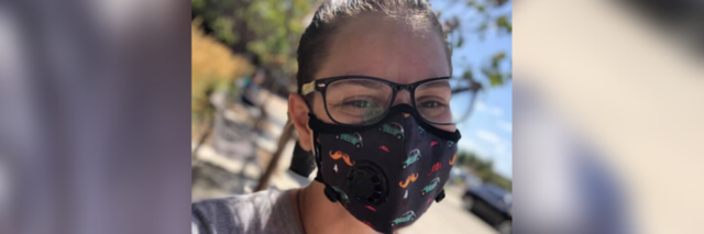 Marisa wearing a Vog mask with a cheerful car pattern on it.