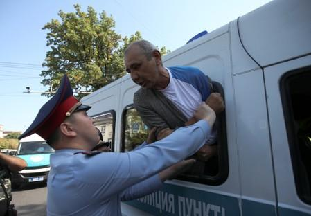 A law enforcement officer detains a man during an anti-government protest in Almaty