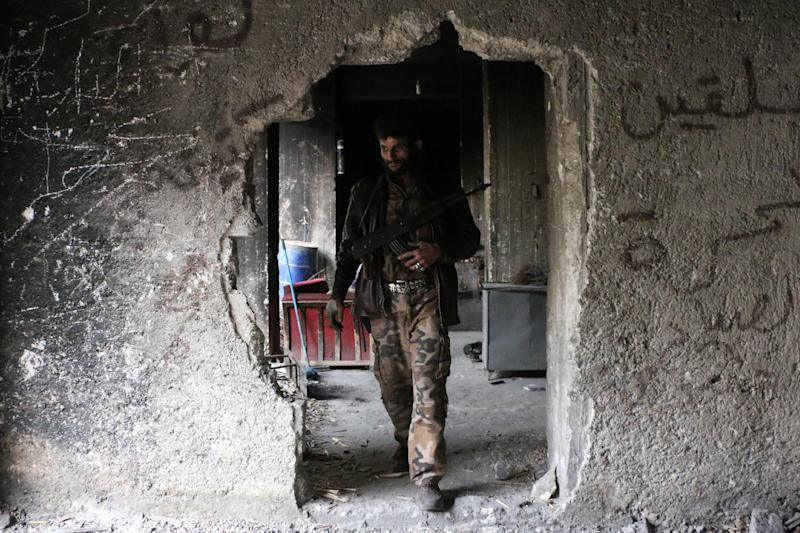 A rebel fighter walks inside a building on October 23, 2014 in Syria's northern city of Aleppo, which has seen opposition forces control most rural areas in northwest Syria's Idlib, and parts of the countryside in Daraa and other provinces (AFP Photo/Fadi al-Halabi)