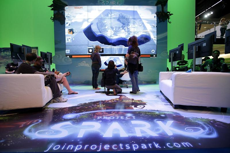 """Show attendee watch a presentation on the video game """"Project Spark"""" at the Microsoft booth during the Electronic Entertainment Expo in Los Angeles, Wednesday, June 12, 2013. (AP Photo/Jae C. Hong)"""