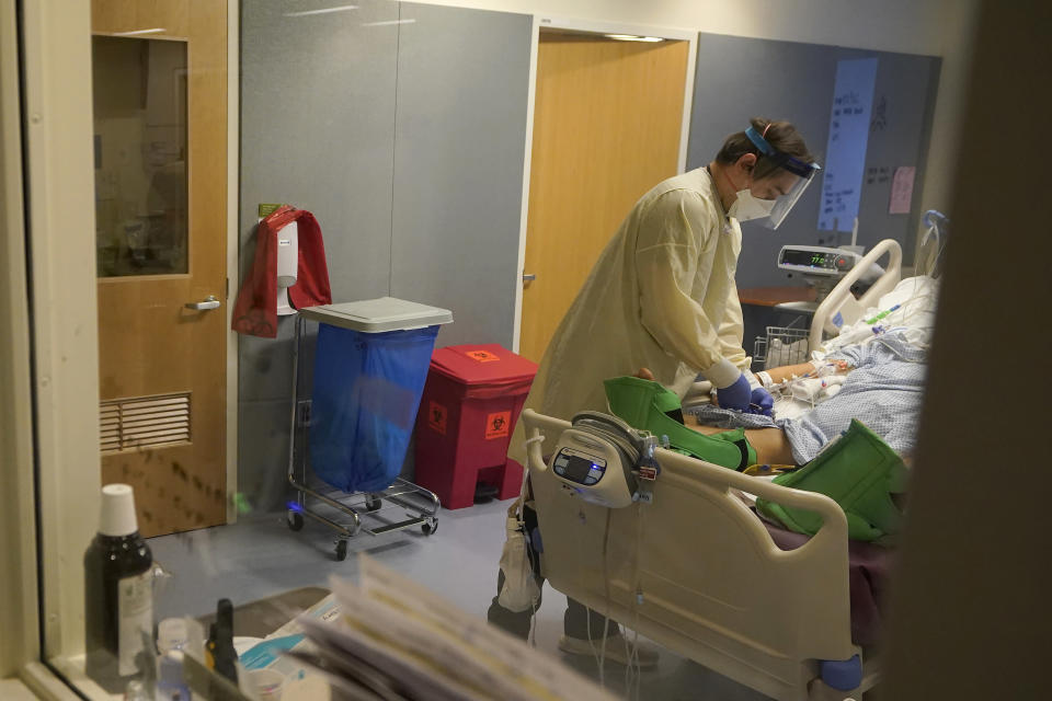 Clinical Nurse Zachary Petterson tends to a COVID-19 patient in the intensive care unit at Santa Clara Valley Medical Center during the coronavirus pandemic in San Jose, Calif., Wednesday, Jan. 13, 2021. (AP Photo/Jeff Chiu)