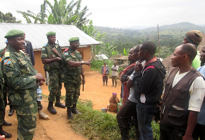 Congolese troops speak with people on January 7, 2016 in Miriki, north of Goma, after 15 people died when Hutu rebels attacked civilians