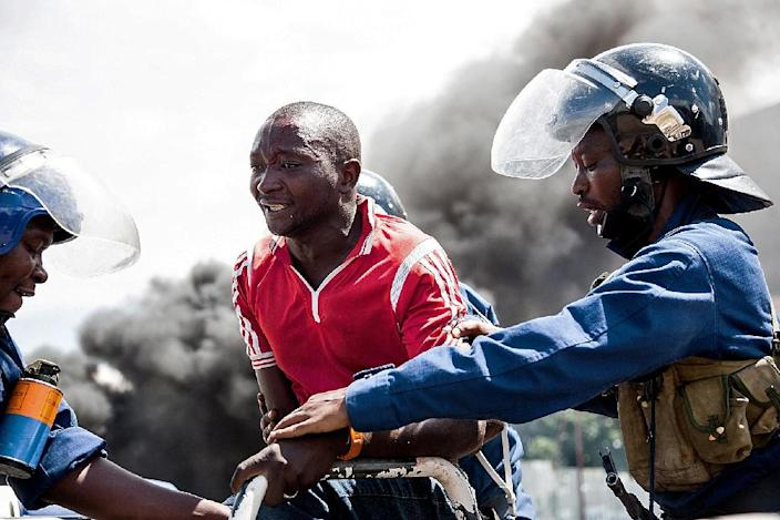 Police officers detain a man during a protest in Bujumbura on May 13, 2015 (AFP Photo/Landry Nshimiye)