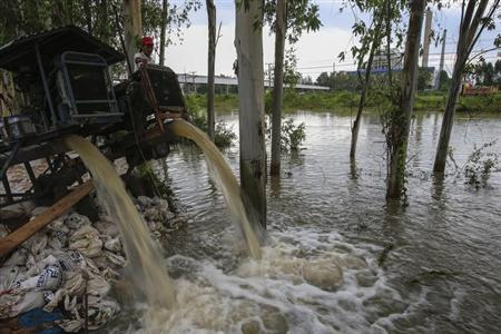 A man looks on as water is pumped out of a canal near 304 Industrial Estate at Srimahaphot district in Prachin Buri September 29, 2013. REUTERS/Athit Perawongmetha