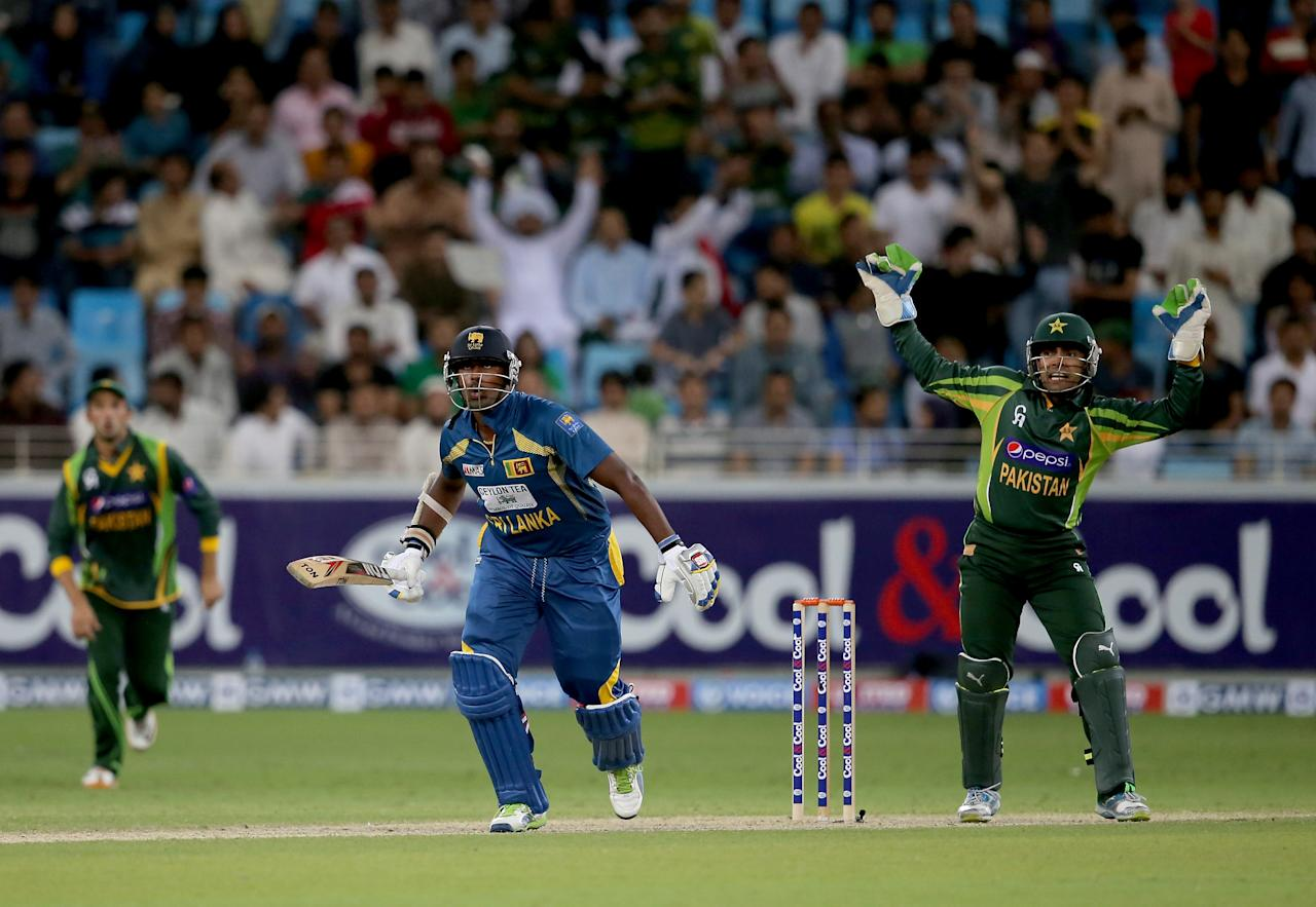 DUBAI, UNITED ARAB EMIRATES - DECEMBER 20:  Thisara Perera of Sri Lanka bats as Umar Akmal of Pakistan looks on during the second One-Day International (ODI ) match between Sri Lanka and Pakistan at the Dubai Sports City Cricket Stadium on December 20, 2013 in Dubai, United Arab Emirates.  (Photo by Francois Nel/Getty Images)