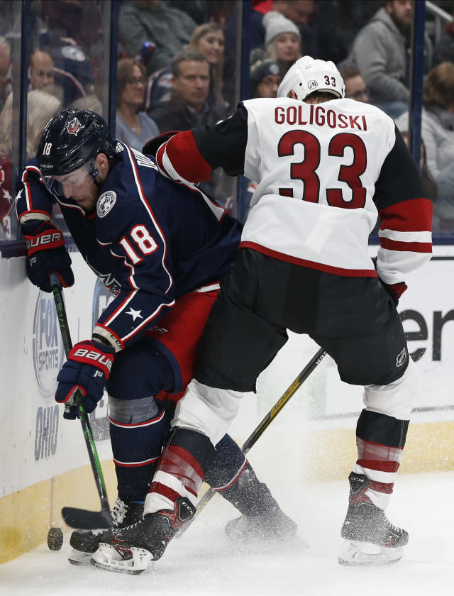 Columbus Blue Jackets' Pierre-Luc Dubois, left, and Arizona Coyotes' Alex Goligoski scrap for the puck during the second period of an NHL hockey game Tuesday, Dec. 3, 2019, in Columbus, Ohio. (AP Photo/Jay LaPrete)