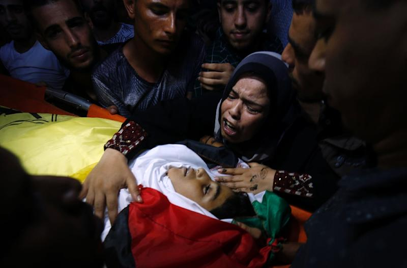 A relative of 12-year-old Palestinian boy Shadi Abdel Aal, who was killed by Israeli forces during a protest at the Israel-Gaza border fence, mourns over his body during his funeral in Jabalia refugee camp in northern Gaza