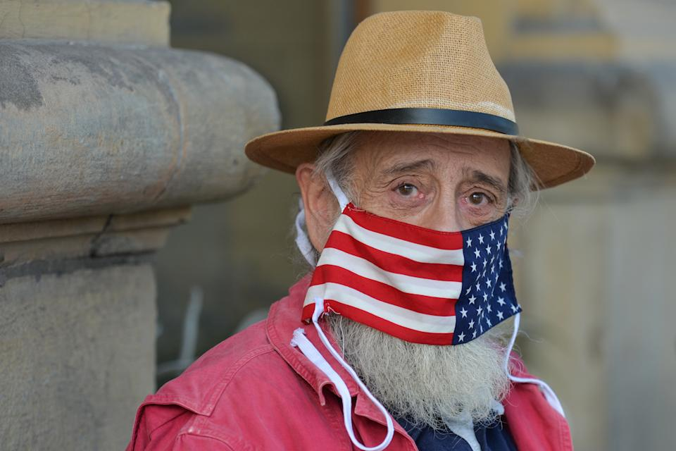 A local man wears a protective face mask with an American flag. An open-air exhibition 'Polish Americans / American Poles' opened in Krakow's Planty Park, organized in cooperation with the Villa Decius Cultural Institute and the US Consulate in Krakow. Throughout October, while walking along the path from Poselska Street to Wawel, visitors and passersby can learn about the stories of famous Americans of Polish origin and their descendants. On Thursday, October 21, 2020, in Krakow, Lesser Poland Voivodeship, Poland. (Photo by Artur Widak/NurPhoto via Getty Images)