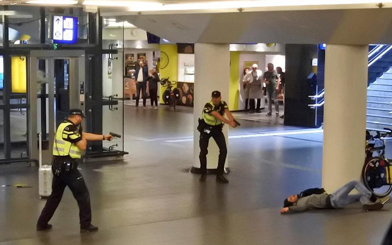 Dutch police officers point their guns at a wounded 19-year-old man who was shot by police after stabbing two people in the central railway station in Amsterdam - Tdwholesale