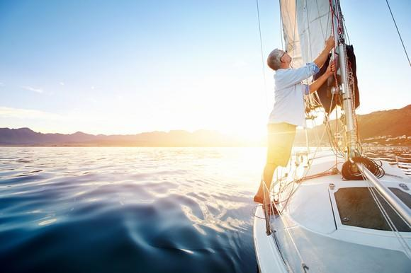 Man fixing the sail on a sailboat that's on open waters.