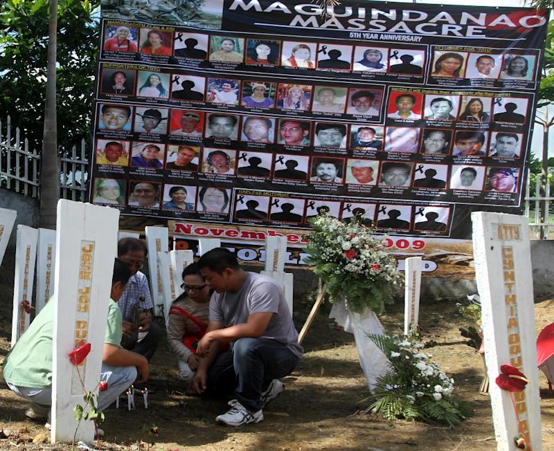 Relatives of the victims of the infamous Maguindanao massacre light candles on wood markers during the fifth year anniversary commemoration at the massacre site on November 23, 2014, in Ampatuan town, southern island of Mindanao
