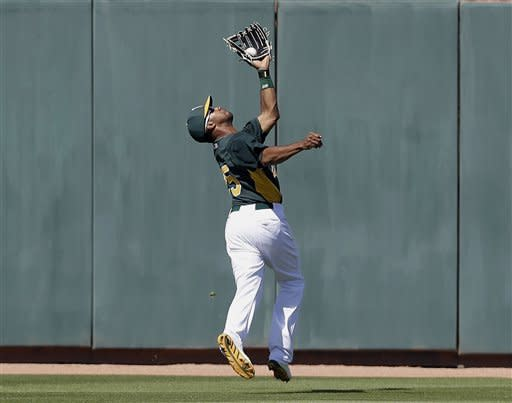 Oakland Athletics left fielder Chris Young makes an over-the-back catch on a pop fly from Milwaukee Brewers' Chris Narveson during the fourth inning of a spring training baseball game on Monday, March 25, 2013 in Phoenix. (AP Photo/Marcio Jose Sanchez)