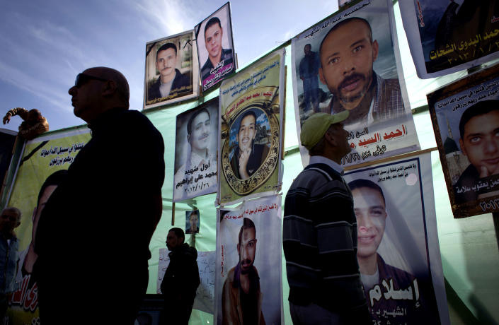 """FILE - In this Thursday, Feb. 21, 2013 file photo, Egyptian men inspect posters of slain men with their pictures and Arabic that reads their names, """"Ahmed el-Syyed, Mohammed Ali Ibrahim, Islam, Osama el-Sherbiny, Ahmed el-Shahat,"""" at a protest camp in front of the provincial government headquarters, unseen, during the fifth day of a general strike, in Port Said, Egypt. Egypt's streets have turned into a daily forum for airing a range of social discontents from labor conditions to fuel shortages and the casualties of myriad clashes over the past two years. Newly called parliamentary elections hold out little hope for plucking the country out of the turmoil and if anything, are likely to just fuel unrest and push it toward economic collapse. (AP Photo/Nasser Nasser, File)"""