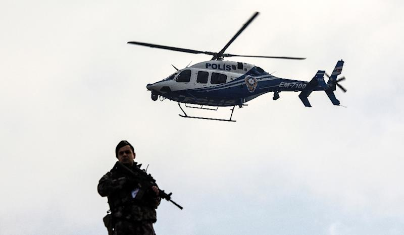 A police helicopter flies over a member of security forces near a courthouse in Mugla, western Turkey, on February 20, 2017