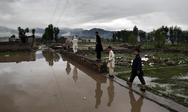 In a Sunday, April 29, 2012 photo, Pakistanis walk on the edge of the flooded road toward the demolished compound of Osama bin Laden, in Abbottabad, Pakistan. One year since U.S. commandos flew into this army town and killed Osama bin Laden, Pakistan has tried to close one of the most notorious chapters in its history. The compound that housed him for six years was razed to the ground, and the wives and children who shared the hideaway were flown to Saudi Arabia just last week. (AP Photo/Muhammed Muheisen)