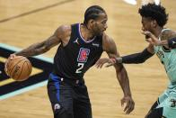 Los Angeles Clippers forward Kawhi Leonard (2) brings the ball up court while guarded by Charlotte Hornets forward Jalen McDaniels during the first half of an NBA basketball game in Charlotte, N.C., Thursday, May 13, 2021. (AP Photo/Jacob Kupferman)