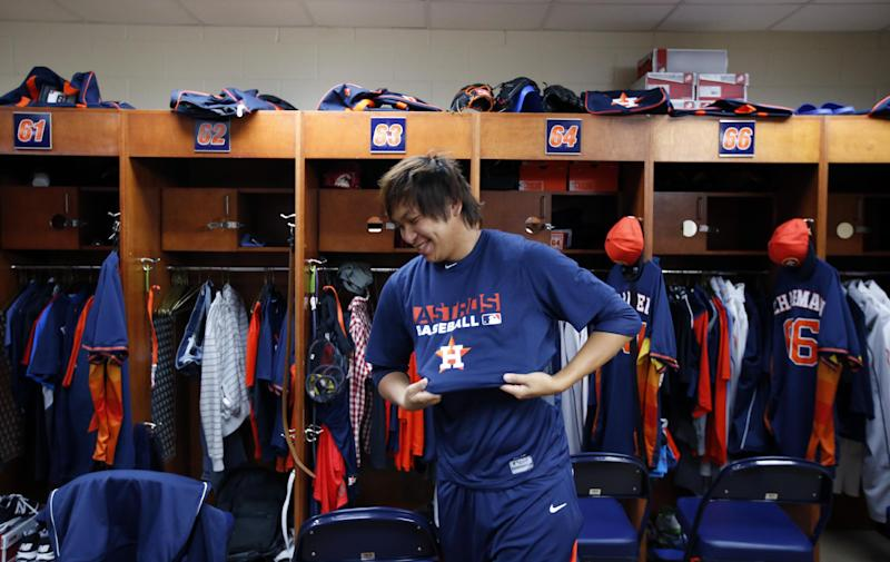 Houston Astros relief pitcher Chia-Jen Lo smiles as he puts on a shirt before a spring training baseball workout, Saturday, Feb. 15, 2014, in Kissimmee, Fla. (AP Photo/Alex Brandon)