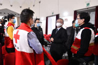 Chinese Ambassador to Italy, Li Junhua, center, talks to a team of Chinese medical experts prior to a news conference at the Red Cross headquarters in Rome, Friday, March 13, 2020. Italy has welcomed a team of Chinese medical experts and 31 tons of ventilators, protective masks and other medical equipment as its fight against coronavirus turns a nation that usually donates aid into one that receives it. For most people, the new coronavirus causes only mild or moderate symptoms. For some it can cause more severe illness. (Alfredo Falcone/LaPresse via AP)