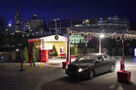 A car drives through Santa's Garage past the social distant Santa, on the roof of a parking garage next to Soldier Field and a backdrop of the Chicago skyline on Dec. 10, 2020. In this socially distant holiday season, Santa Claus is still coming to towns (and shopping malls) across America but with a few 2020 rules in effect. (AP Photo/Charles Rex Arbogast)