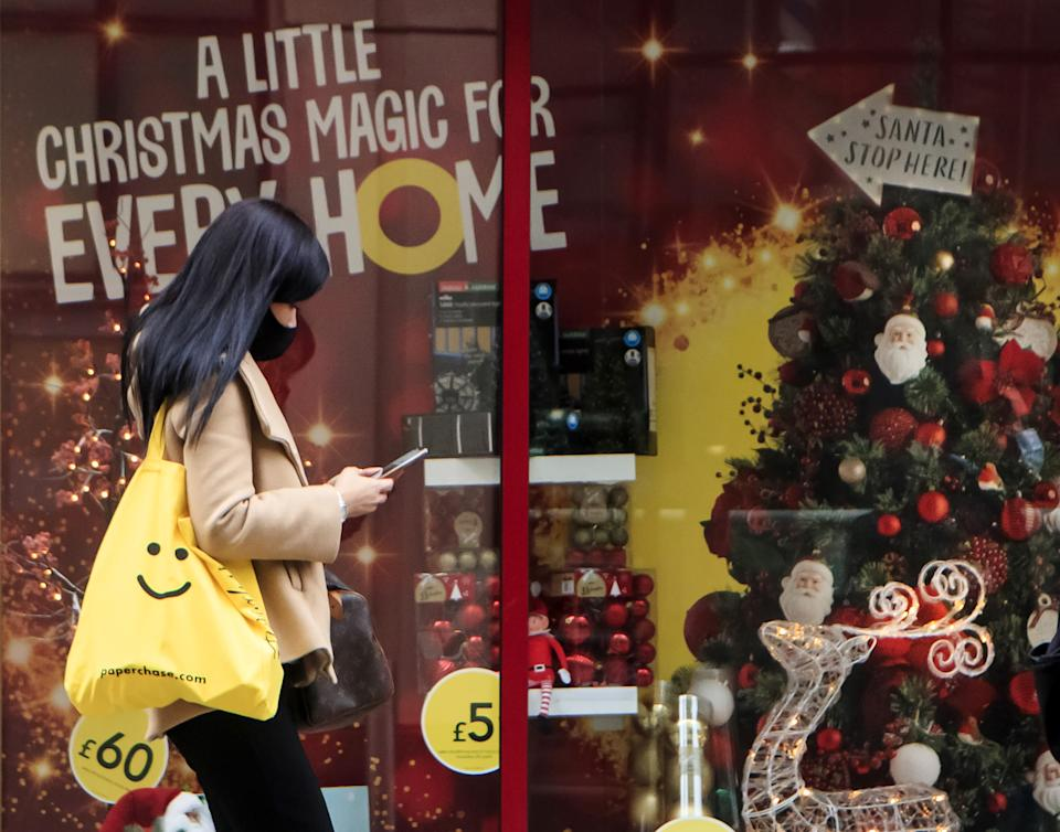 A woman walks past a Christmas display in a shop window in Leeds, Yorkshire, as England continues a four week national lockdown to curb the spread of coronavirus.
