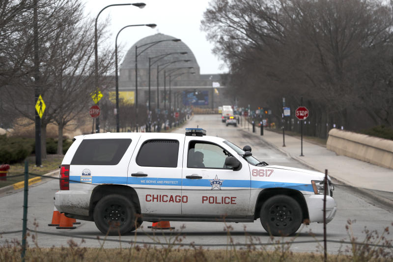 A Chicago police officer blocks the road to the Adler Planetarium along Lake Michigan Thursday, March 26, 2020, in Chicago. On Thursday morning, Chicago Police began turning joggers and others away from the city's lakefront trails amid fears of the spread of the coronavirus, hours after Mayor Lori Lightfoot threatened to shut them down if people would not stop crowding the areas. (AP Photo/Charles Rex Arbogast)