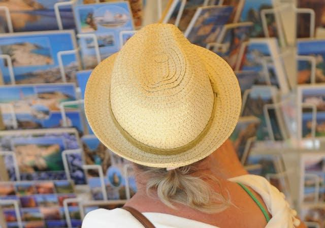 A woman looking at holiday postcards in Praia da Luz, Portugal